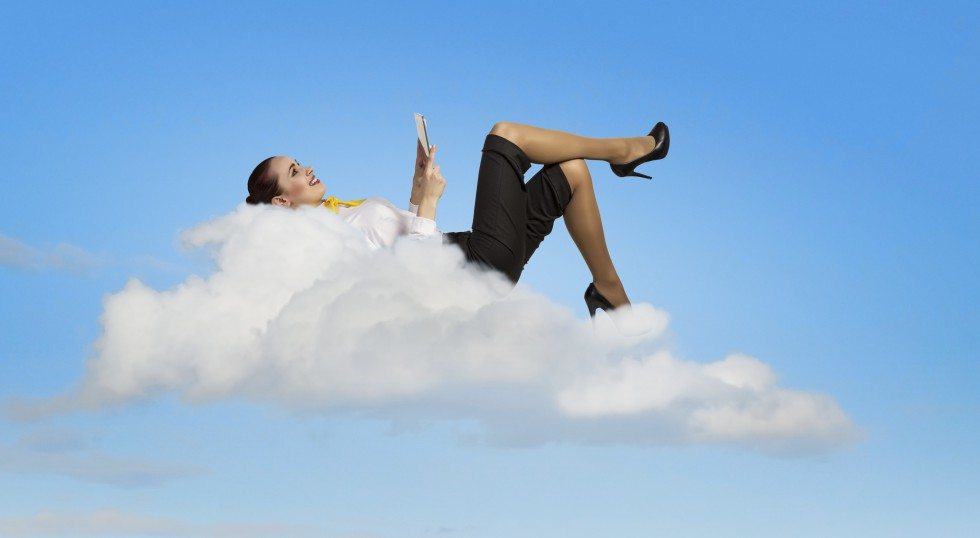 Image of businesswoman lying on clouds with tablet pc